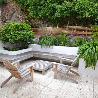 Kleiner Moderner Garten im Sommer, hinter dem Haus mit direkter Sonneneinstrahlung, Natursteinplatten und Kübelpflanzen in London