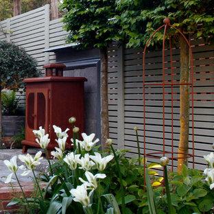 Geometrische, Kleine, Halbschattige Stilmix Gartenkamin im Sommer, hinter dem Haus mit Natursteinplatten in Kent