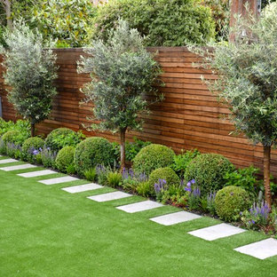 This is an example of a medium sized classic back garden in London with a living wall and natural stone paving.