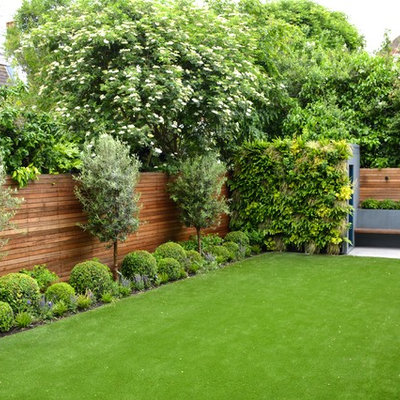 Design ideas for a mid-sized contemporary full sun backyard stone landscaping in London.