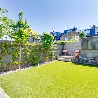 Ejemplo de jardín actual, en patio trasero, con jardín vertical, exposición parcial al sol y entablado