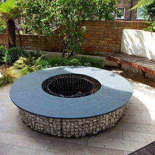 Mittelgroßer Moderner Garten hinter dem Haus mit Feuerstelle und Natursteinplatten in London