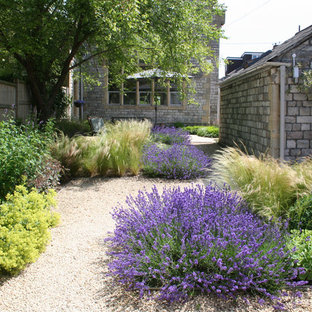 This is an example of a rustic formal garden for spring in Other with gravel.