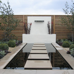 Inspiration for a contemporary full sun garden in Other with a pond and concrete paving.