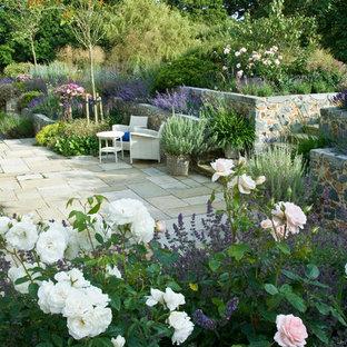 Пример оригинального дизайна: большой солнечный, летний участок и сад на заднем дворе в стиле кантри с подпорной стенкой, освещенностью и покрытием из каменной брусчатки