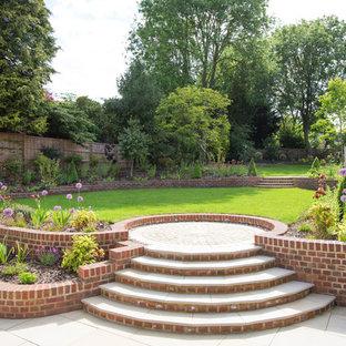 Exempel på en stor klassisk formell trädgård i full sol i slänt, med marksten i tegel