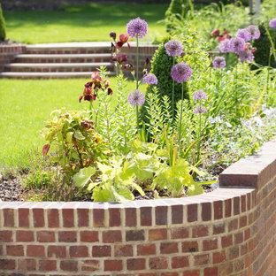 Immagine di un grande giardino formale classico esposto in pieno sole con un pendio, una collina o una riva e pavimentazioni in mattoni