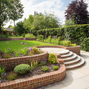 Inspiration for a large traditional full sun formal garden in Hertfordshire with a retaining wall.