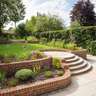 Идея дизайна: большой геометрический, солнечный участок и сад в классическом стиле с хорошей освещенностью и подпорной стенкой