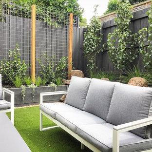 Exempel på en liten modern bakgård i full sol som tål torka på våren, med en stödmur och marktäckning