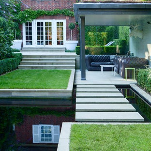 Inspiration for a medium sized contemporary back full sun garden in London with natural stone paving and a pond.