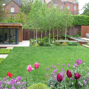 Large contemporary back formal partial sun garden in London with a water feature and natural stone paving.