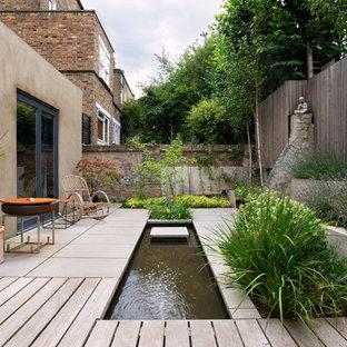 Cette image montre un petit jardin à la française arrière asiatique l'été avec un bassin, une exposition partiellement ombragée et des pavés en pierre naturelle.