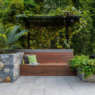Design ideas for a large tropical backyard partial sun garden for summer in Sunshine Coast with natural stone pavers and a retaining wall.