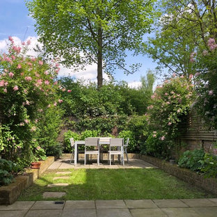 Classic back garden in London with concrete paving.
