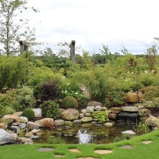 Exempel på en mycket stor lantlig formell trädgård i full sol längs med huset på hösten, med en damm