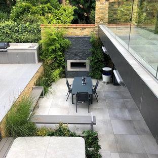Geometrische, Mittelgroße, Halbschattige Moderne Gartenkamin im Sommer, hinter dem Haus mit Natursteinplatten in London