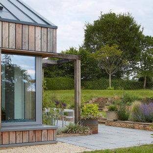 Exemple d'un jardin arrière scandinave de taille moyenne avec une exposition ensoleillée et des pavés en pierre naturelle.