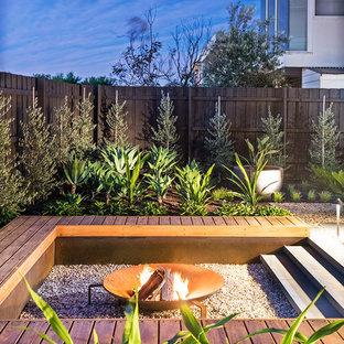Свежая идея для дизайна: солнечный участок и сад среднего размера на заднем дворе в современном стиле с местом для костра, освещенностью и покрытием из гравия - отличное фото интерьера