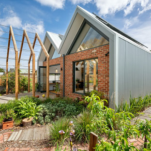 Inspiration for a contemporary backyard full sun garden in Melbourne with brick pavers and a wood fence.