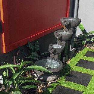 Esempio di un piccolo giardino formale tropicale esposto in pieno sole in cortile con fontane e pavimentazioni in pietra naturale