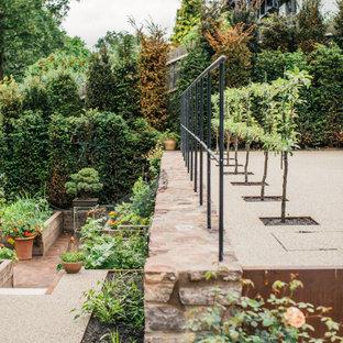 Aménagement d'un grand jardin à la française arrière scandinave l'été avec une entrée ou une allée de jardin, une exposition ensoleillée et du gravier.