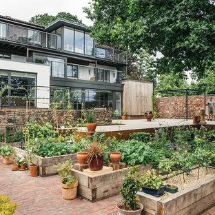 Новые идеи обустройства дома: большой солнечный, летний огород на участке на заднем дворе в скандинавском стиле с освещенностью и мощением клинкерной брусчаткой
