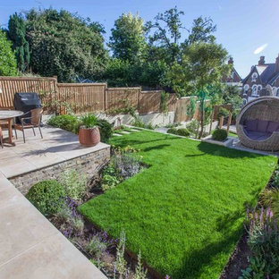 This is an example of a large contemporary back garden in Hampshire with natural stone paving.