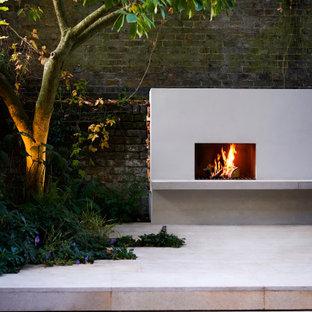 Kleiner, Halbschattiger Moderner Garten hinter dem Haus mit Kamin und Dielen in London
