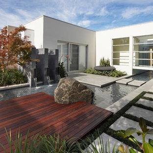 Aménagement d'un jardin avec une terrasse en bois ou composite contemporain avec un point d'eau.