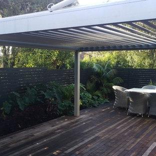 Idee per un giardino formale design esposto in pieno sole di medie dimensioni e dietro casa in inverno con un muro di contenimento e pedane
