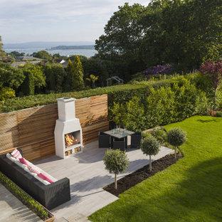 Geometrischer, Großer Moderner Garten im Sommer mit Kamin, direkter Sonneneinstrahlung und Betonplatten in Glasgow
