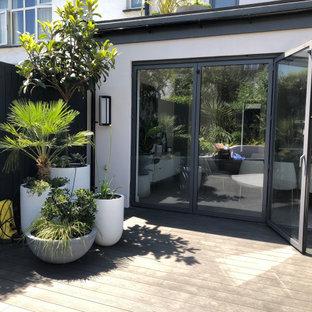 Geometrischer, Kleiner Moderner Garten im Sommer, hinter dem Haus mit Kamin, direkter Sonneneinstrahlung und Dielen in London