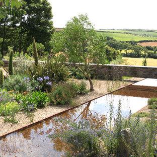 Rustik inredning av en mycket stor trädgård i delvis sol i slänt, med en fontän och grus