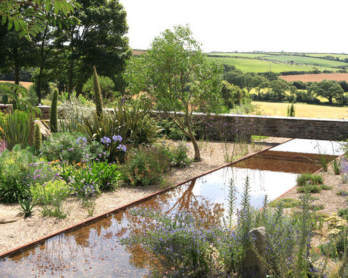 Photo Of An Expansive Rustic Sloped Partial Sun Garden In Cornwall With A Water Feature And