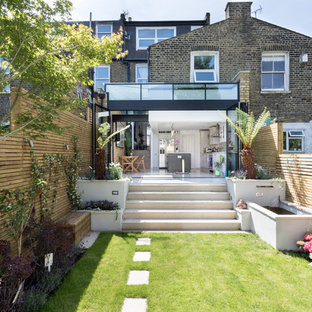 Medium sized contemporary back formal full sun garden for summer in London with natural stone paving.
