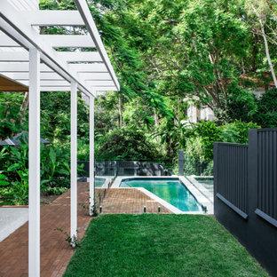 Cette image montre un petit jardin design avec des solutions pour vis-à-vis, une exposition partiellement ombragée et des pavés en brique.