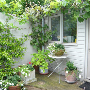 Inspiration for a small classic back formal garden in London with a potted garden and decking.