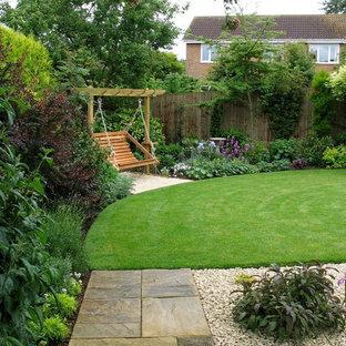 Diseño de jardín tradicional, de tamaño medio, en verano, en patio trasero, con exposición total al sol y gravilla