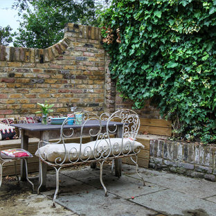 Design ideas for a small shabby-chic style partial sun backyard stone landscaping in London.