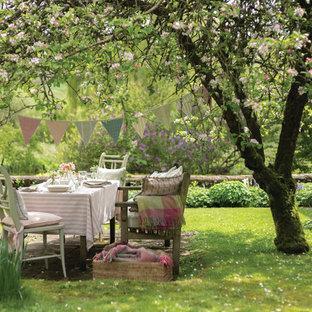 Diseño de jardín romántico, grande, en primavera, en patio trasero, con exposición reducida al sol y adoquines de piedra natural
