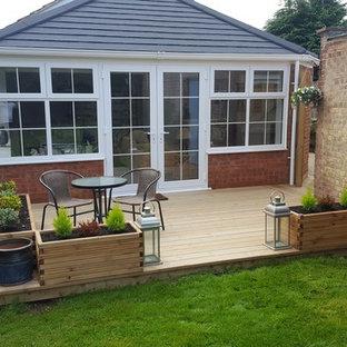 Idée de décoration pour un petit jardin avec une terrasse en bois ou composite arrière nordique l'été avec une exposition partiellement ombragée.