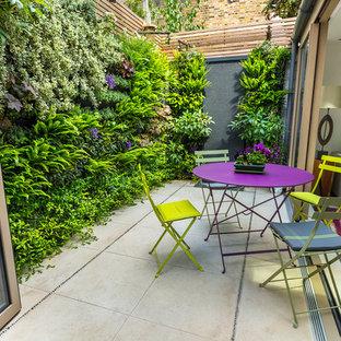 Immagine di un piccolo giardino minimal esposto a mezz'ombra dietro casa in estate con pavimentazioni in pietra naturale
