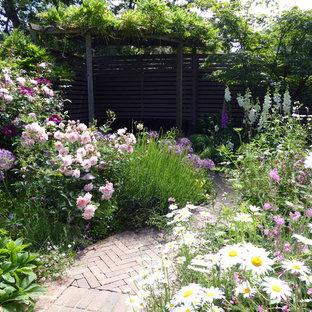 Réalisation d'un petit jardin arrière champêtre l'été avec une entrée ou une allée de jardin, une exposition ensoleillée et des pavés en brique.