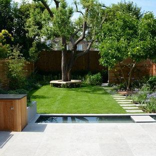 Mittelgroßer, Geometrischer Moderner Garten im Sommer, hinter dem Haus mit Teich, direkter Sonneneinstrahlung und Natursteinplatten in London