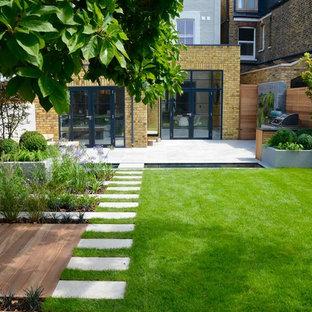 Mittelgroßer Moderner Garten im Sommer, hinter dem Haus mit Teich, direkter Sonneneinstrahlung und Natursteinplatten in London