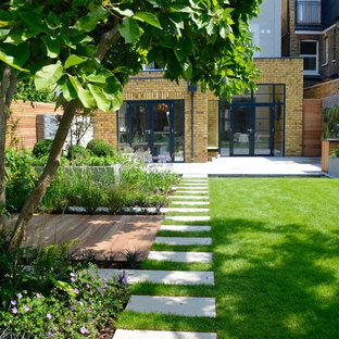 Photo of a medium sized contemporary back full sun garden for summer in London with a pond and natural stone paving.