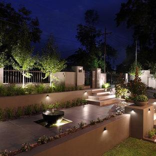 Idee per un grande giardino formale design esposto a mezz'ombra davanti casa in inverno con un muro di contenimento e pavimentazioni in pietra naturale