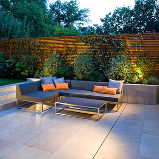 Medium sized contemporary back partial sun garden in London with natural stone paving.