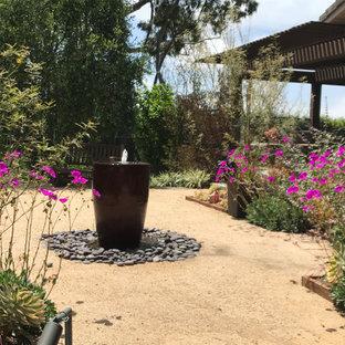 Cette image montre un jardin design de taille moyenne et l'été avec une entrée ou une allée de jardin, une exposition ensoleillée et un gravier de granite.
